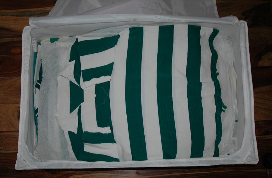 uma camisola antiga na caixa, entre papel anti-ácido